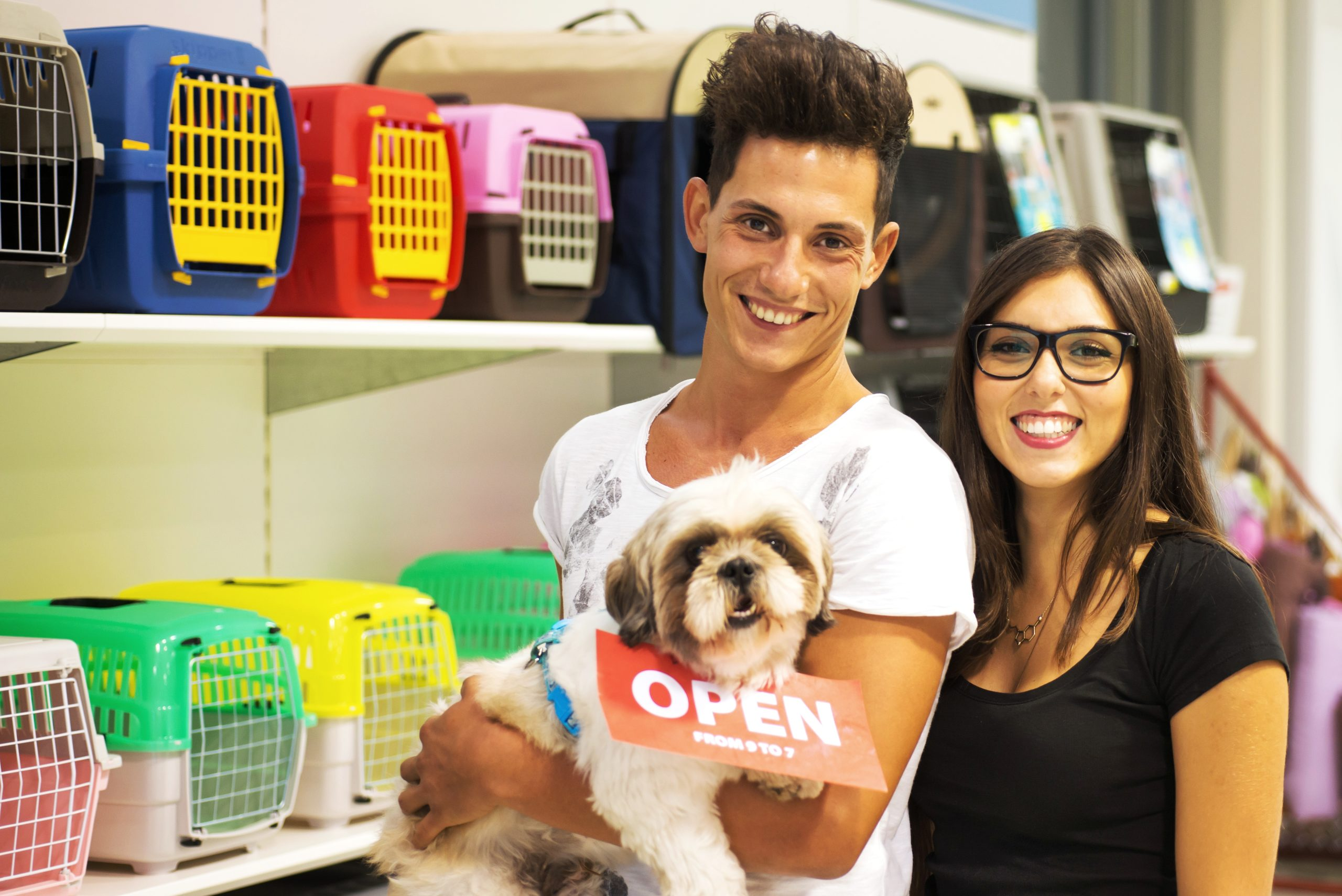 Couple and Dog in Pet Shop. Transportation Case on Background